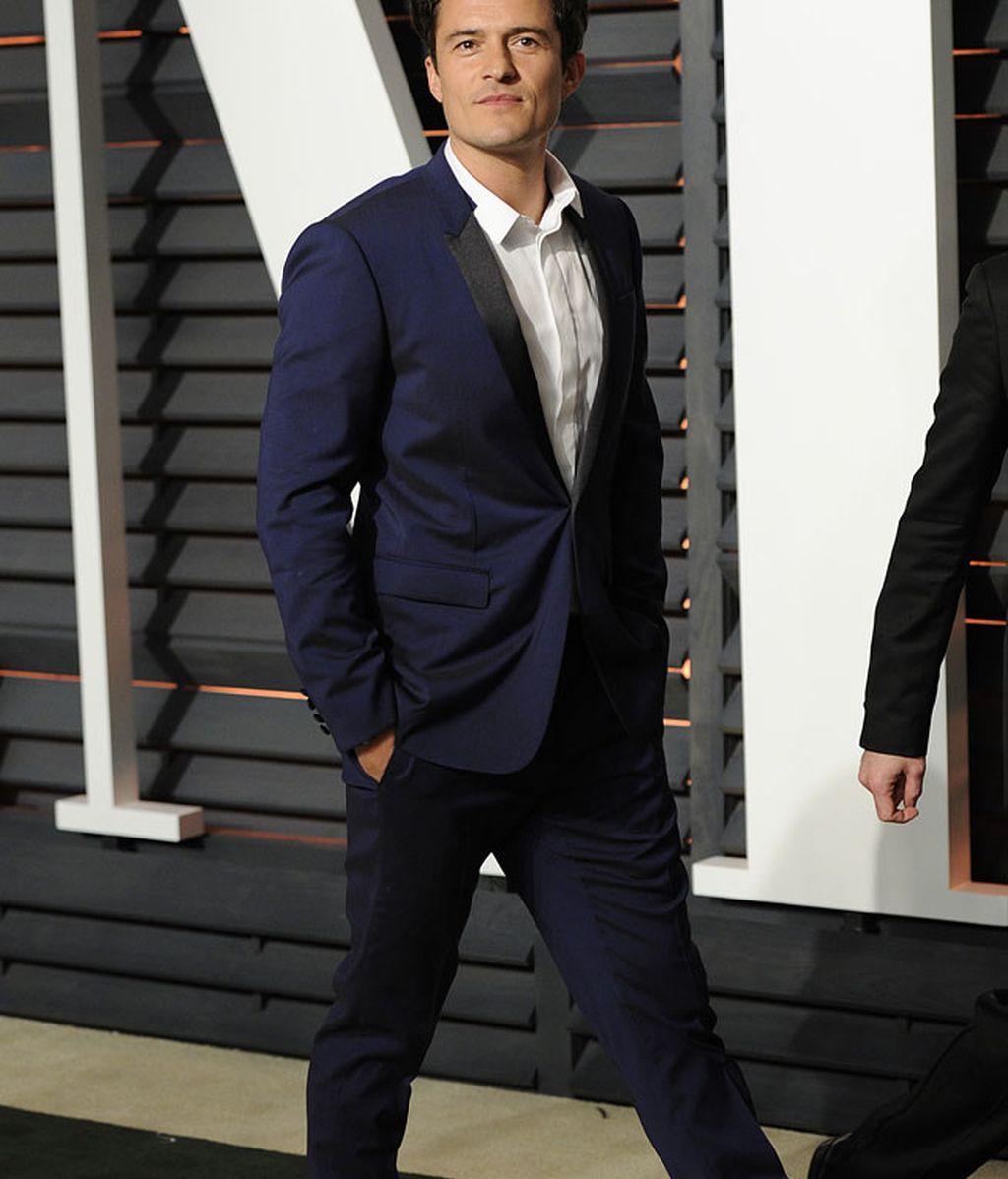 Orlando Bloom con traje azul marino y camisa blanca