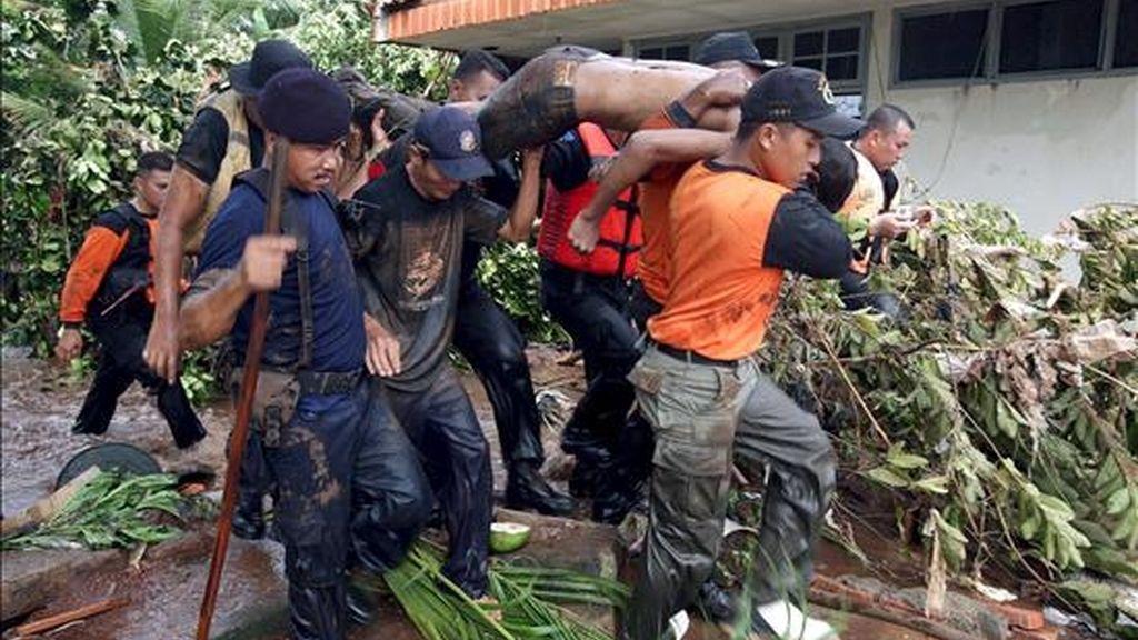 Miembros de los equipos de rescate evacuan el cadáver de un hombre muerto en una riada originada por la rotura de una presa en Yakarta, Indonesia, hoy viernes 27 de marzo. EFE