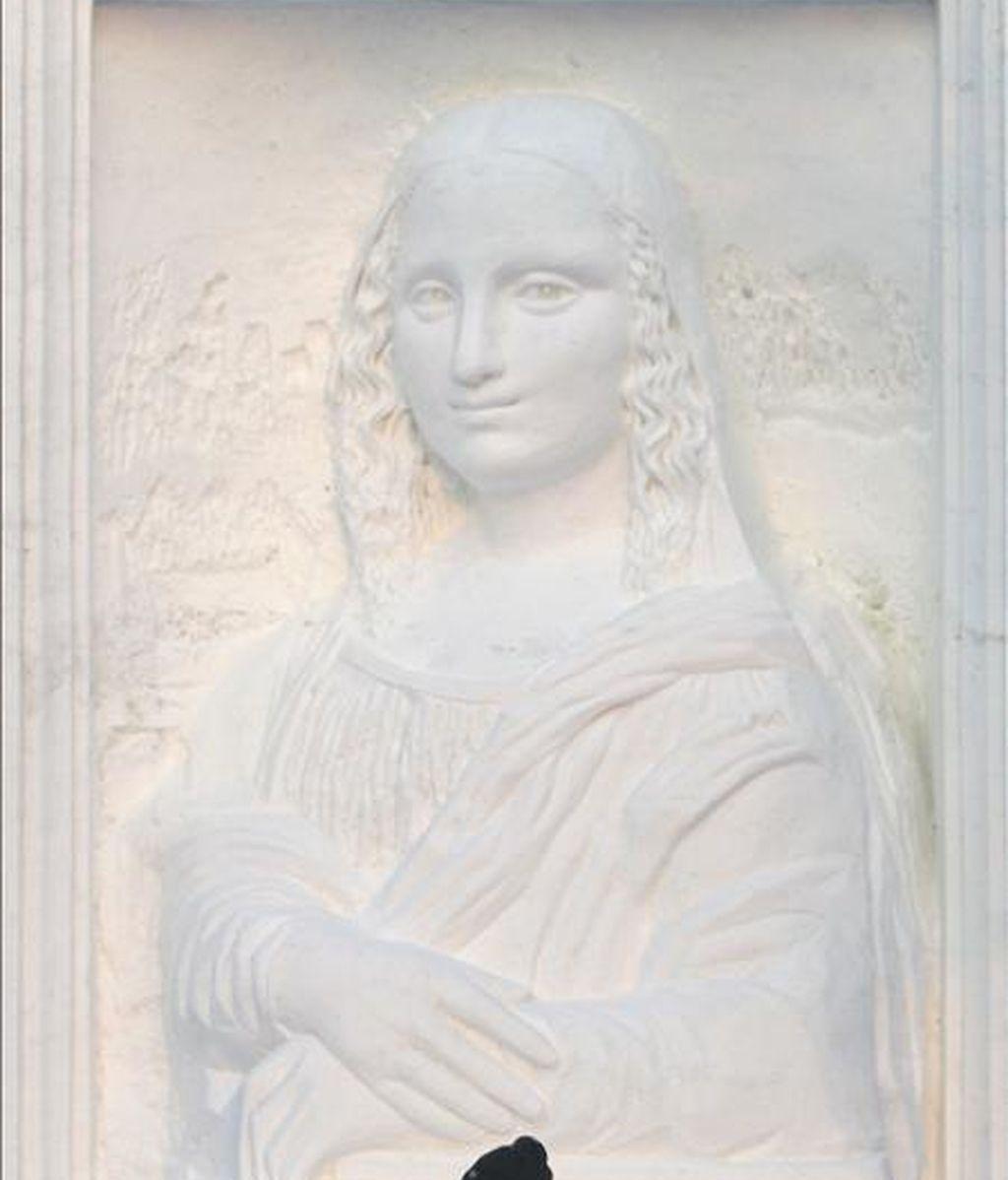 """Un hombre pasa frente a una réplica de la """"Mona Lisa"""" de Leonardo da Vinci, una de las gigantescas estatuas de nieve y agua helada que anualmente se esculpen para ser las estrellas del Festival de la Nieve y el Hielo, una fiesta que comienza hoy y durará varios meses, en la ciudad de Harbin, donde los termómetros pueden llegar hasta los 40 grados bajo cero, en el extremo norte de China. EFE"""