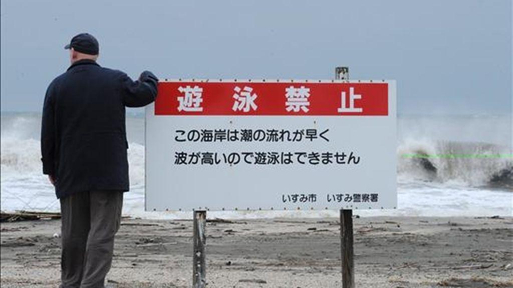 Un hombre japonés observa una playa junto a una señal de alerta por fuerte oleaje en la ciudad de Isumi, en la provincia de Chiba. EFE/Archivo