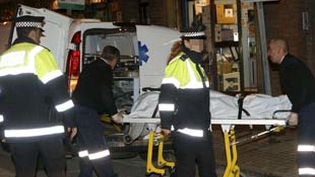 Técnicos de los servicios de Emergencias trasladan el cadáver de la mujer presuntamente asesinada en L´Hospitalet por su hermano. Foto: EFE.