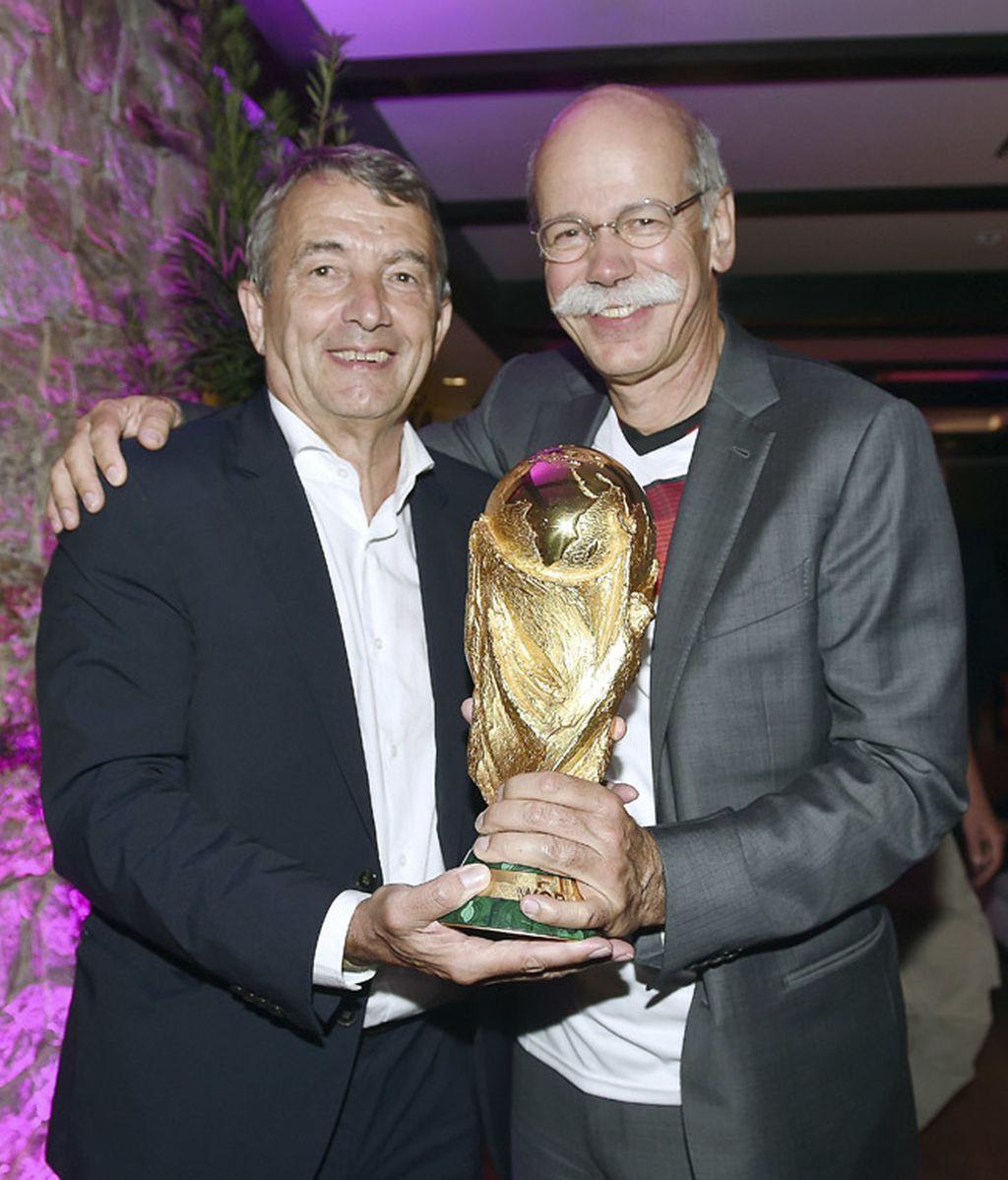 El presidente de la Federación Alemana posa con la Copa junto a uno de los patrocinadores
