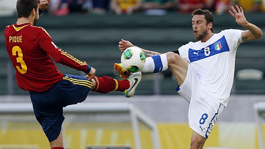 Piqué disputa un balón ante un jugador italiano