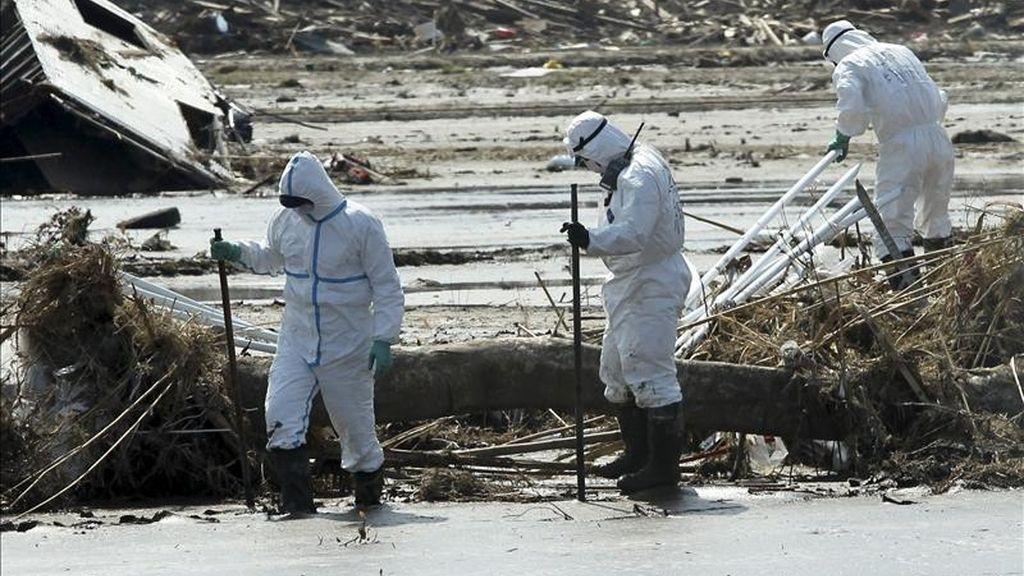 Policías protegidos de la radiación buscan víctimas del tsunami en Minamisoma en la prefectura de Fukushima (Japón). EFE/Archivo