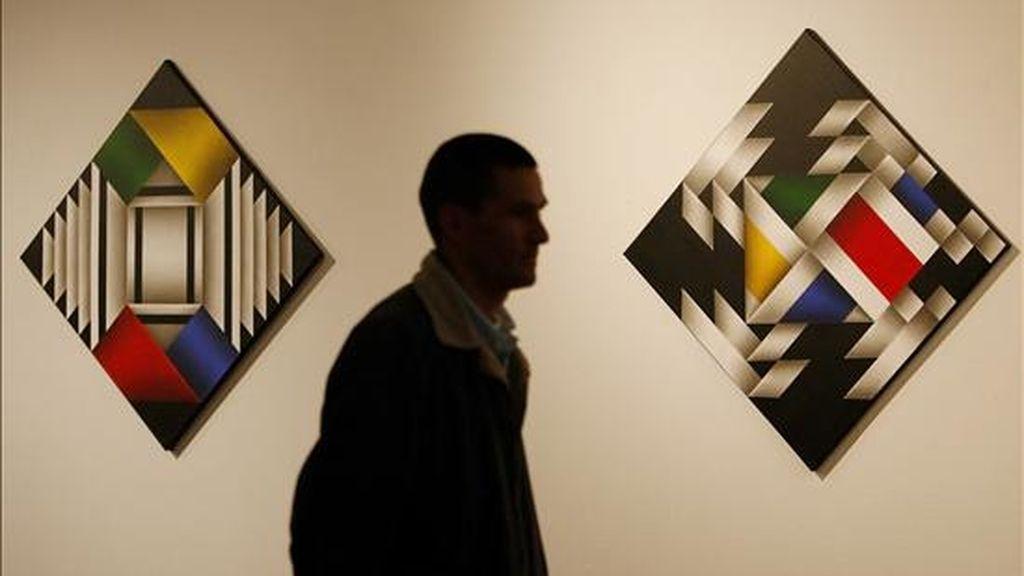 """Fotografía en la que se observa a un hombre caminando junto a dos obras del pintor colombiano Ómar Rayo en Bogotá (Colombia). Rayo dijo en entrevista concedida a EFE que tras """"escapar de la muerte"""" ahora pinta """"con todo el abecedario"""". EFE"""