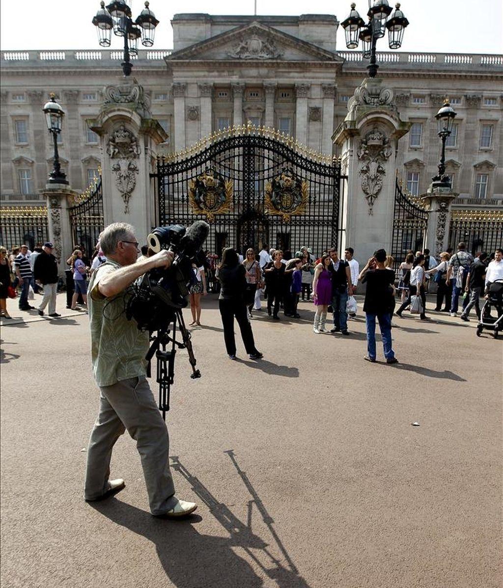 Un camarógrafo frente al balcón principal del palacio de Buckingham hoy. Esta residencia real británica será uno de los escenarios principales de la  boda del príncipe Guillermo de Inglaterra y Kate Middleton el próximo día 29. EFE