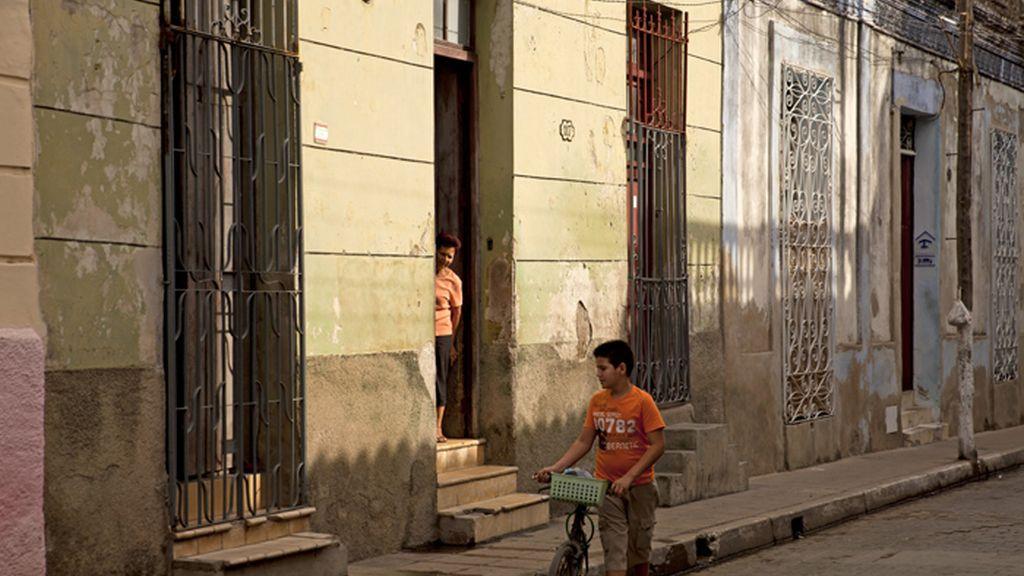 Un niño pasea con su bicicleta por la calle