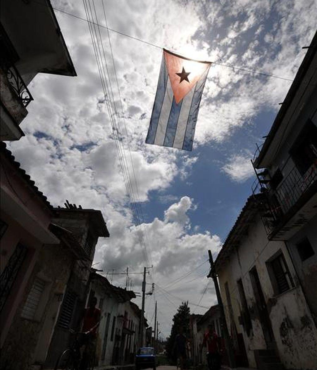 Varias personas caminan por una calle adornada con banderas cubanas en Santa Clara, un día antes de celebrase en esta ciudad el acto central por el Día de la Rebeldía Nacional. EFE