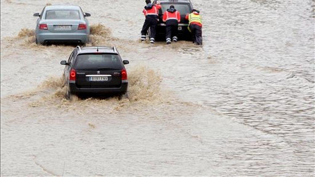 En la imagen, tres operarios de la autopista empujan a uno de los coches que quedó bloqueado por el agua en la A-8, a su paso por Bilbao, a causa de las intensas lluvias caidas a finales del mes pasado. EFE