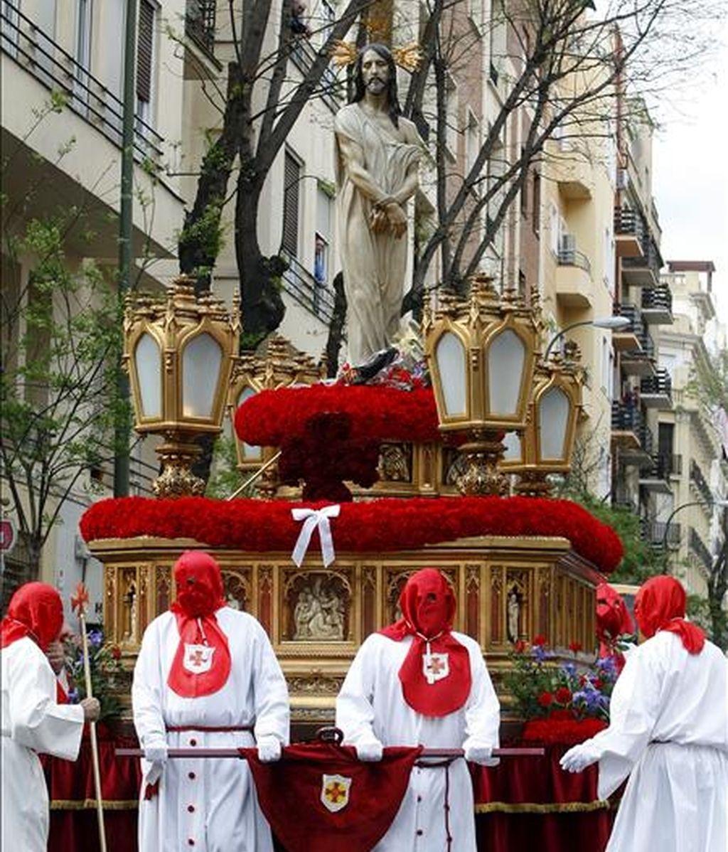 Varios cofrades trasladan la imagen del Divino Cautivo, en la que es visible un lazo blanco contra el aborto, durante la procesión que ha tenido lugar esta tarde en Madrid dentro del Jueves Santo. EFE