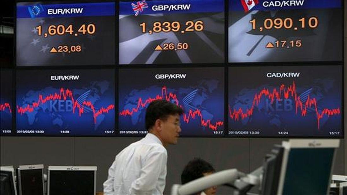 Un agente del banco surcoreano Korean Exchange Bank pasa frente a unos monitores de resultados en la Bolsa de Seúl. EFE/Archivo