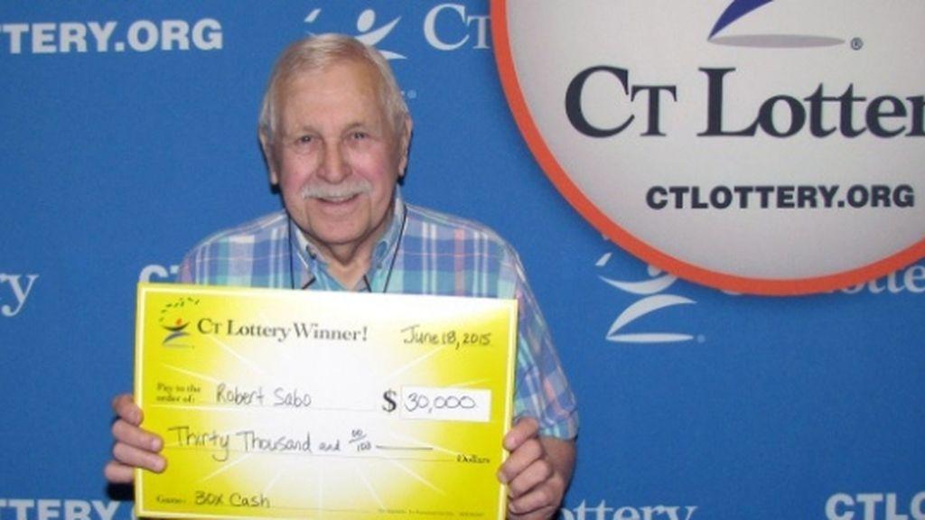 Bob Sabo posa con su premio de la lotería