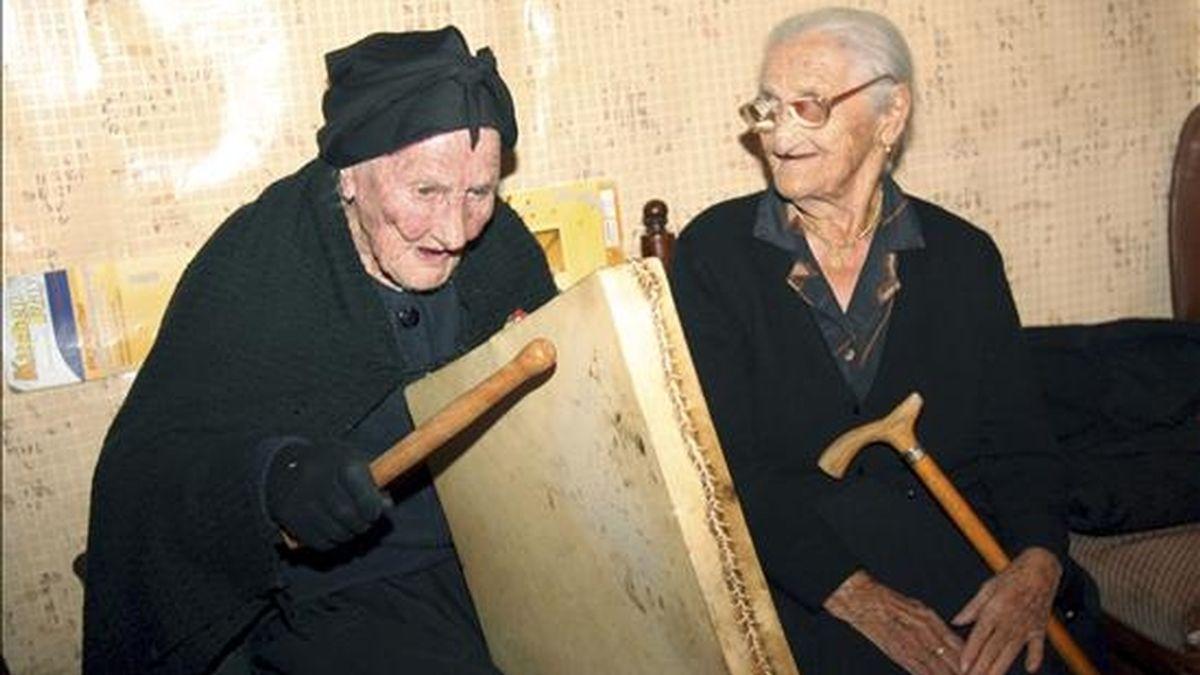 Gregoria Benito (i), natural y vecina de Peñaparda (Salamanca), cumple 106 años, la popular Tía Gora mantiene entre sus aficiones diarias tocar el pandero cuadrado, un instrumento de percusión típico de esta localidad. En la imagen, acompañada de su amiga y vecina, Dionisia Morales, de 104 años. EFE
