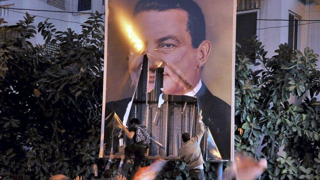 En la imagen, un grupo de manifestantes retirando un cartel con la imagen del ex presidente egipcio Hosni Mubarak durante una protesta en Alejandría, Egipto. EFE/Archivo