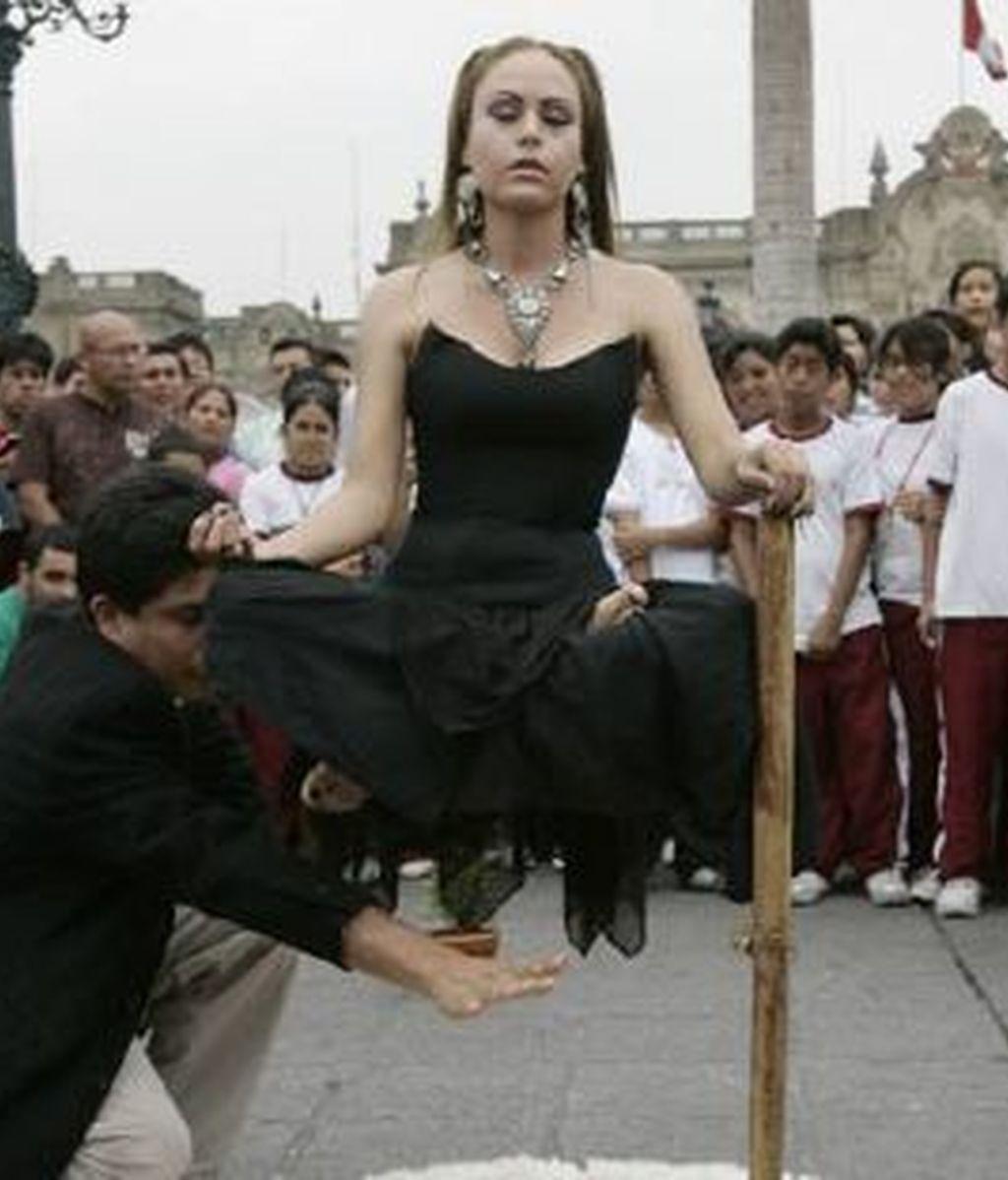 """La ilusionista peruana Claudia Pacheco """"Princesa Inca"""" realiza un acto de levitación hoy, 27 de marzo de 2009, en la Plaza de Armas de Lima (Perú). Foto: EFE"""