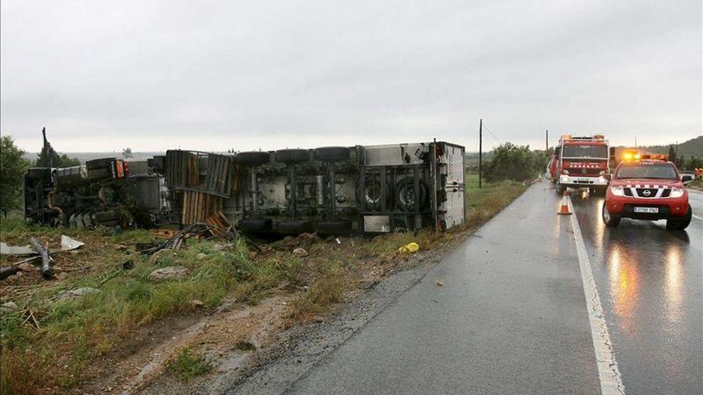 Servicios de emergencia junto a un camión volcado, uno de los tres vehículos de estas características implicados en un accidente múltiple en la carretera N-340, a la altura de Amposta (Tarragona) que, aunque sin heridos de gravedad, ha obligado a cerrar la vía. EFE