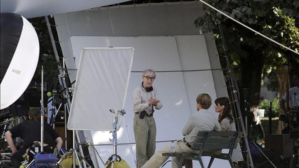 """El director estadounidense Woody Allen (c) habla con la primera dama francesa Carla Bruni-Sarkozy (d) y el actor estadounidense Owen Wilson (2-d) en la plaza Juan XXIII, detrás de la catedral de Notre Dame, durante el rodaje de la más reciente película de su película, """"Media noche en París"""". EFE"""