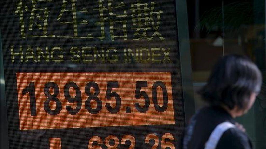 Una mujer camina frente a un tablero electrónico con los resultados del índice Hang Seng de la Bolsa de Hong Kong. EFE/Archivo