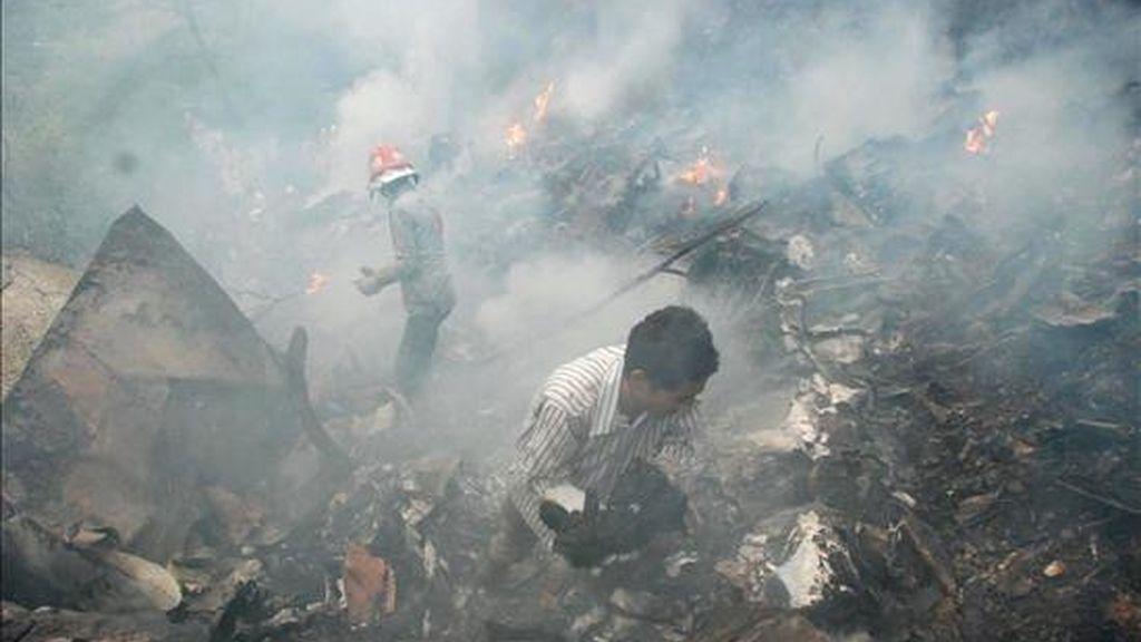 Empleados de los servicios de rescate trabajando en la zona en la que se estrelló este miércoles un avión de la compañía aérea privada Air Blue en Islamabad. Los 152 ocupantes del avión han fallecido. EFE