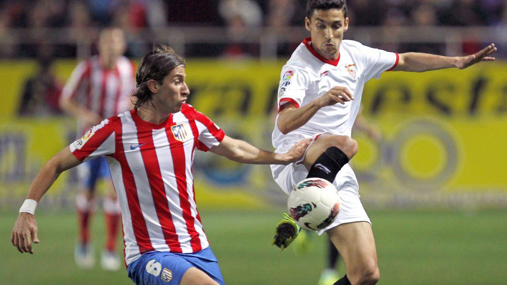 El delantero del Sevilla Jesús Navas lucha el balón con el brasileño Filipe Luis, del Atlético de Madrid.