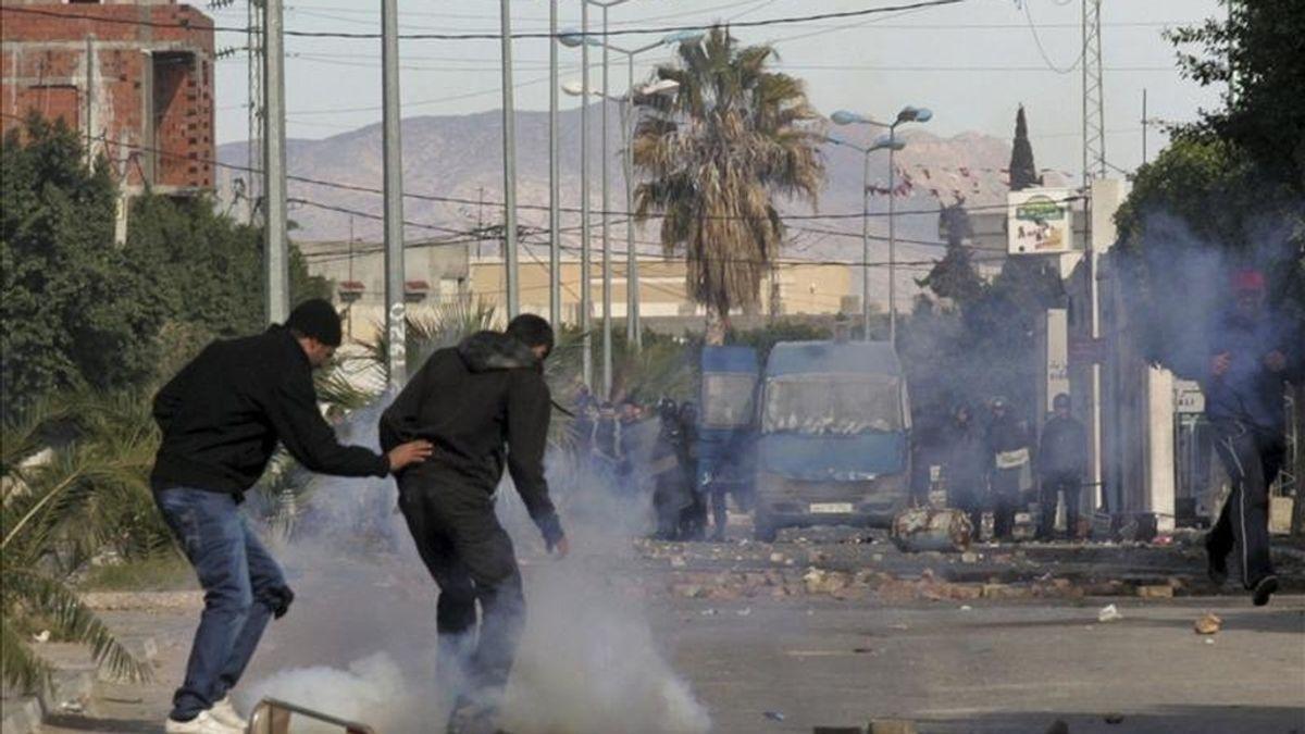Jóvenes intentan esquivar las bombas de gases lacrimógenos lanzadas por policías durante unos violentos enfrentamientos vividos al término de una protesta contra el paro y la exclusión social, en Regueb, Túnez. EFE