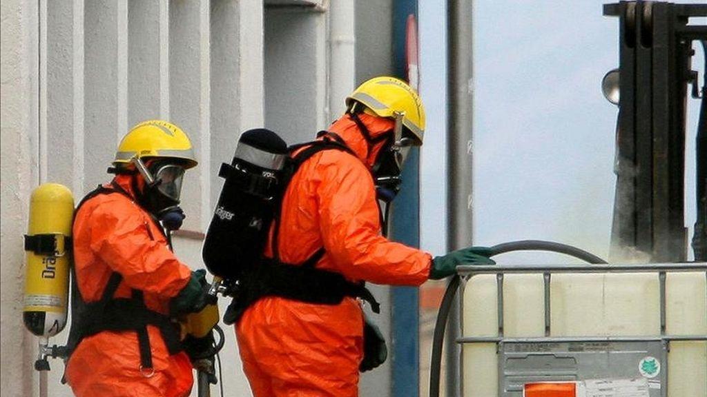 Bomberos con equipos especiales trabajan para controlar una fuga de vapor liberada en las instalaciones de una empresa textil de Tortosa (Tarragona), tras una pequeña explosión causada por una mezcla accidental de clorito de sosa y ácido clorhídrico en junio de 2006. EFE/Archivo