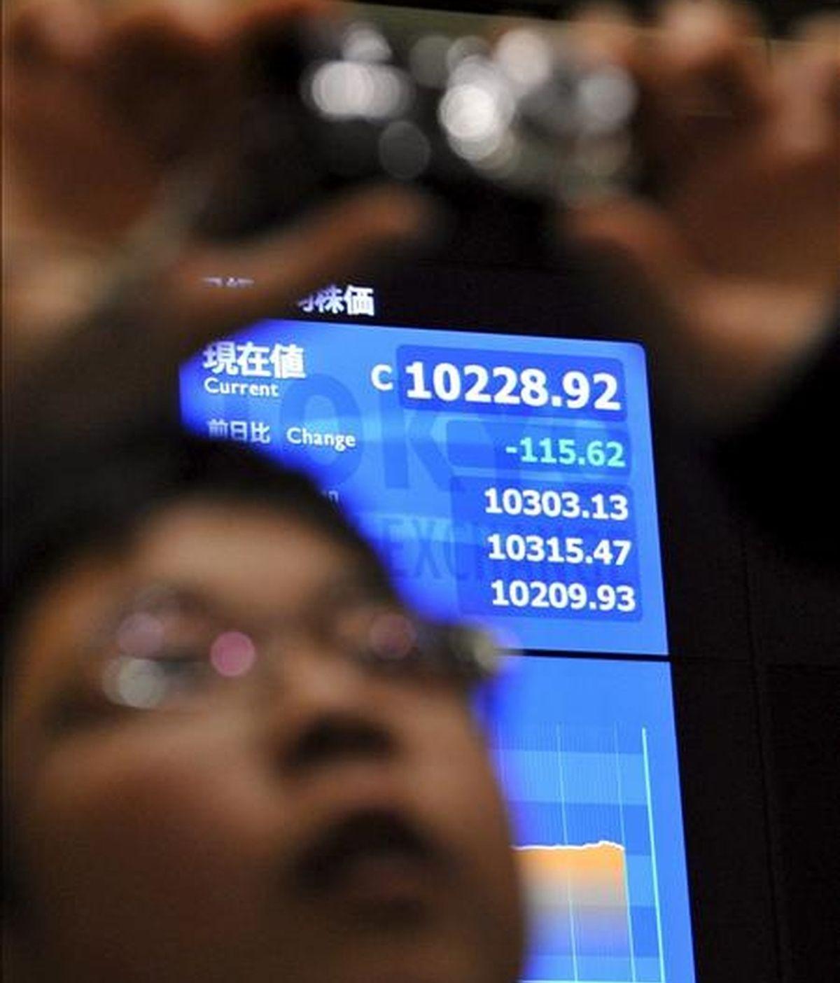 Un visitante de la Bolsa de Valores de Tokio realiza una foto durante la última jornada mercantil del año en Tokio. EFE/Archivo