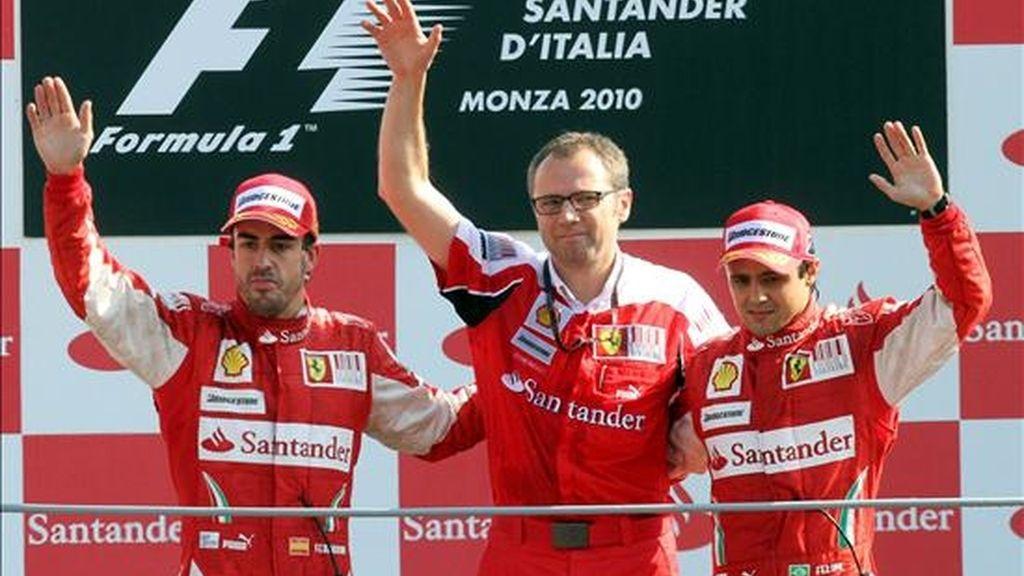 De izquierda a derecha, el piloto español Fernando Alonso (Ferrari), el director deportivo de Ferrari, Stefano Domenicali, y el piloto brasileño Felipe Massa (Ferrari) saludan desde el podio después del Gran Premio de Italia de Fórmula Uno en Monza (Italia) el pasado 12 de septiembre. EFE/Archivo