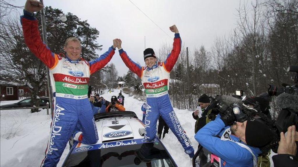 El piloto finlandés Mikko Hirvonen (d) y su copiloto Jarmo Lehtilnen (i) celebran su victoria tras ganar, abordo del Ford Fiesta RS, la última jornada del rally de Suecia, primera cita del Mundial, en Hagfors, Suecia. EFE