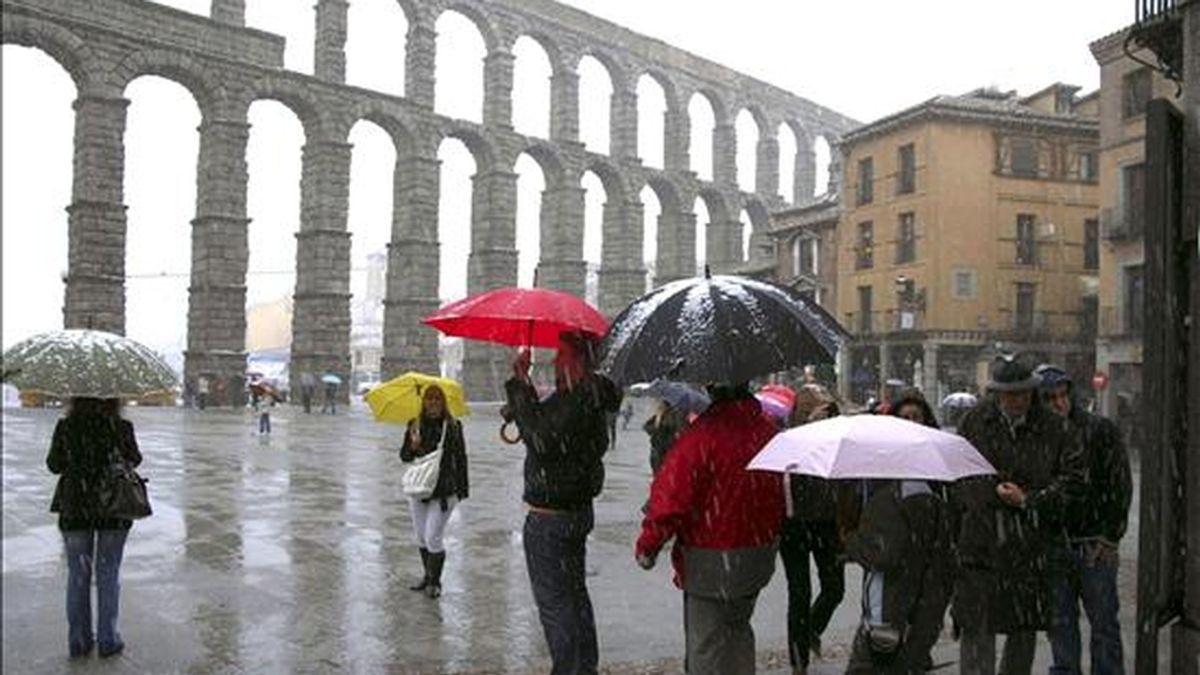 Varios turistas hacen fotografías junto al Acueducto de Segovia mientras nieva en la capital. EFE/Archivo