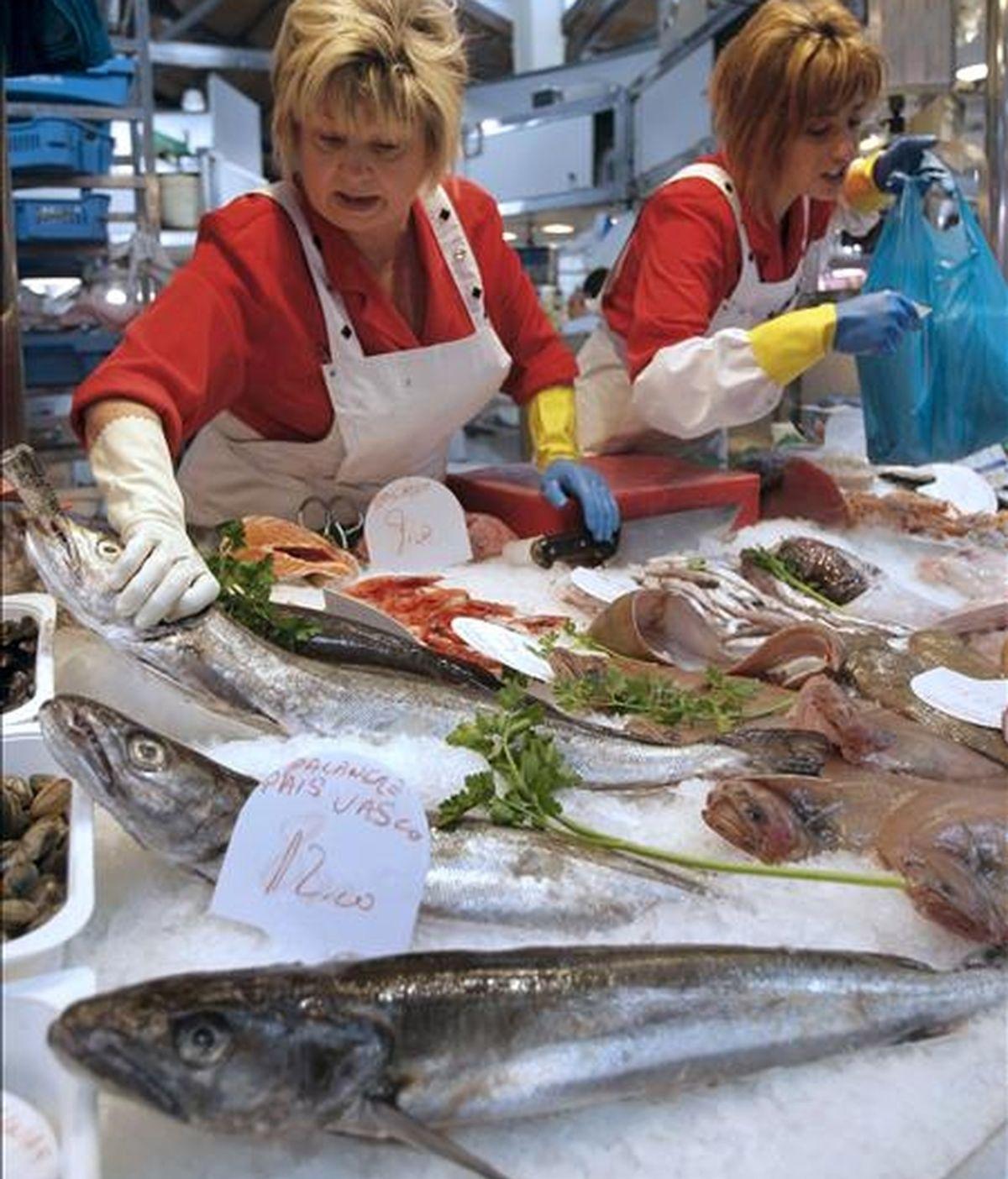 Una pescadera vende una merluza en un mercado de Barcelona. EFE/Archivo