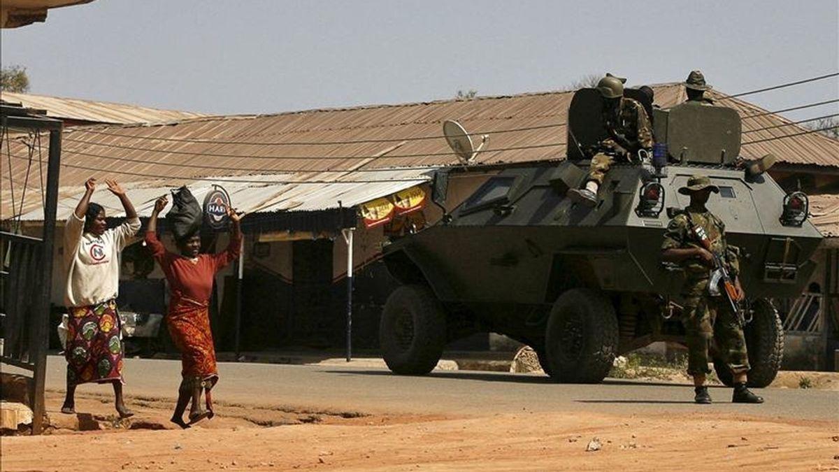 Mujeres nigerianas alzan los brazos al pasar junto un tanque con soldados, en la ciudad nigeriana de Jos, epicentro de enfrentamientos entre musulmanes y cristianos,  en enero de 2010. EFE/Archivo