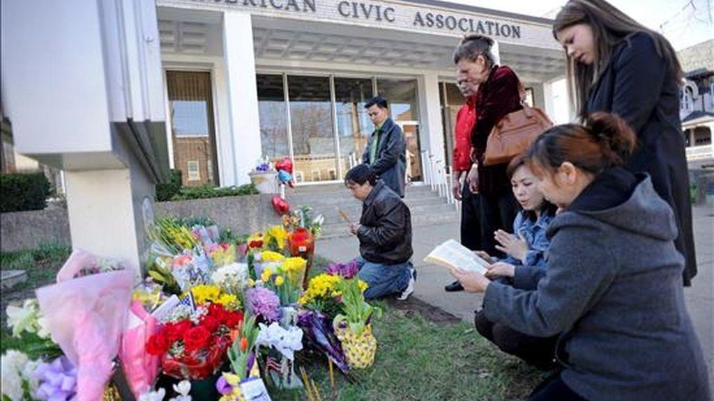 Un grupo de personas reza hoy junto a un sepulcro temporal a las afueras del edificio de la Asociación Cívica Americana de Binghamton, Nueva York (EE.UU.), donde un hombre armado asesinó a 13 personas antes de quitarse la vida. EFE
