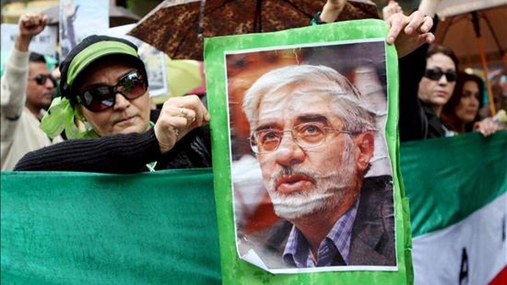 Una manifestante muestra un retrato del candidato a la presidencia iraní Mir Husein Musaví durante un acto de protesta por las presuntas irregularidades en las elecciones en Irán, en Hamburgo, Alemania, el pasado 20 de junio. EFE/Archivo