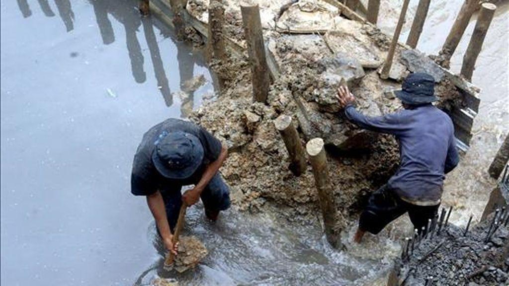 Dos trabajadores indonesios construyen una presa en Yakarta. EFE/ARCHIVO