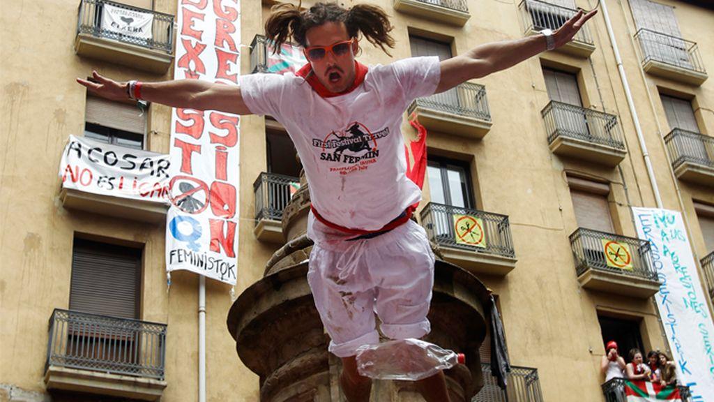 Un jóven juerguista salta desde la fuente de la Plaza Navarrería, una peligrosa costumbre en el inicio de los san fermines