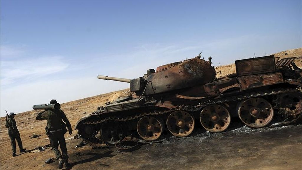 Rebeldes libios junto a un tanque supuestamente destruido por los bombardeos aéreos de la OTAN, en un punto de control hoy en la localidad de Ajdabiya. EFE