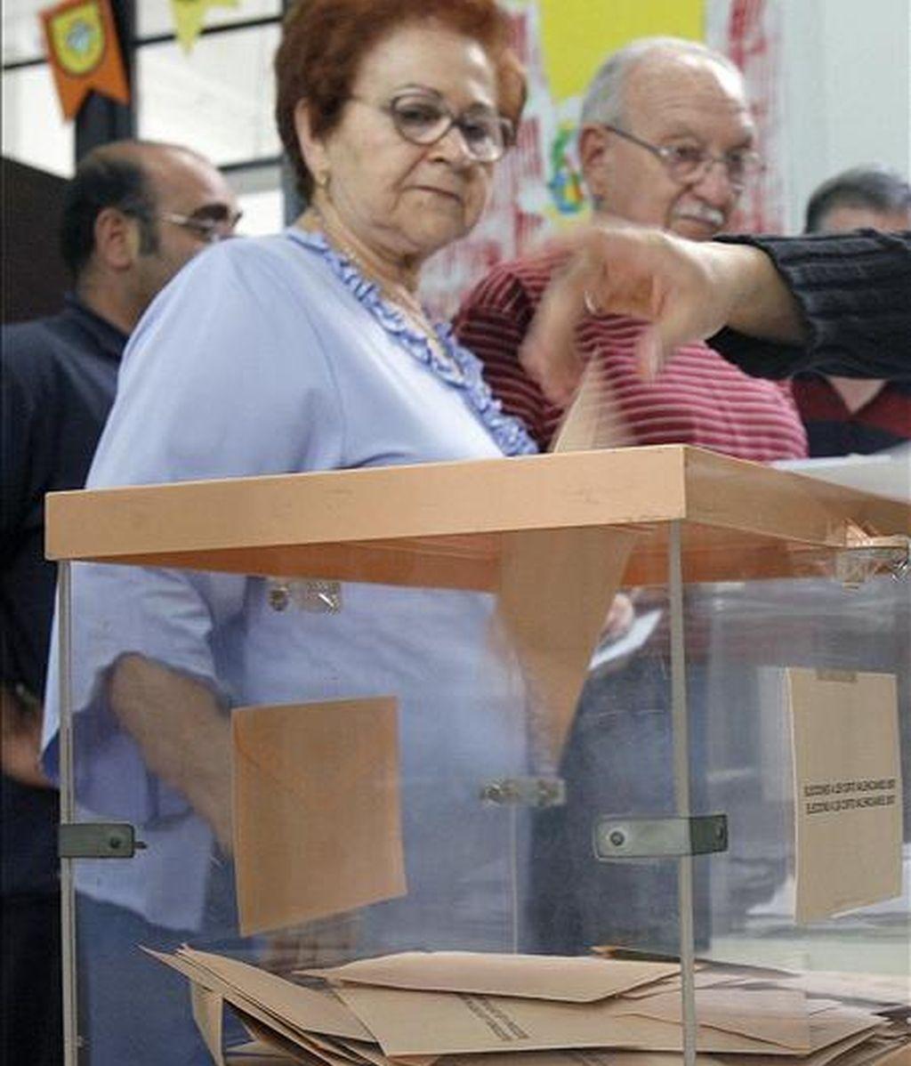 Una mujer observa como la presidenta de la mesa electoral deposita su voto en una en Valencia. EFE/Archivo