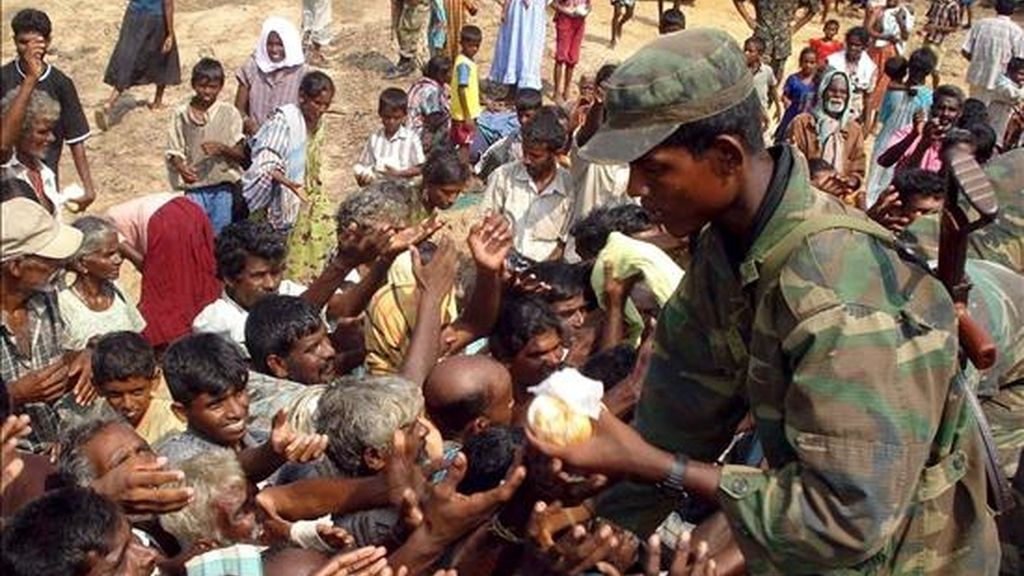 Un militar reparte comida entre los miles de civiles desplazados que viven en centros temporales en Puthumattalan, Sri Lanka. EFE