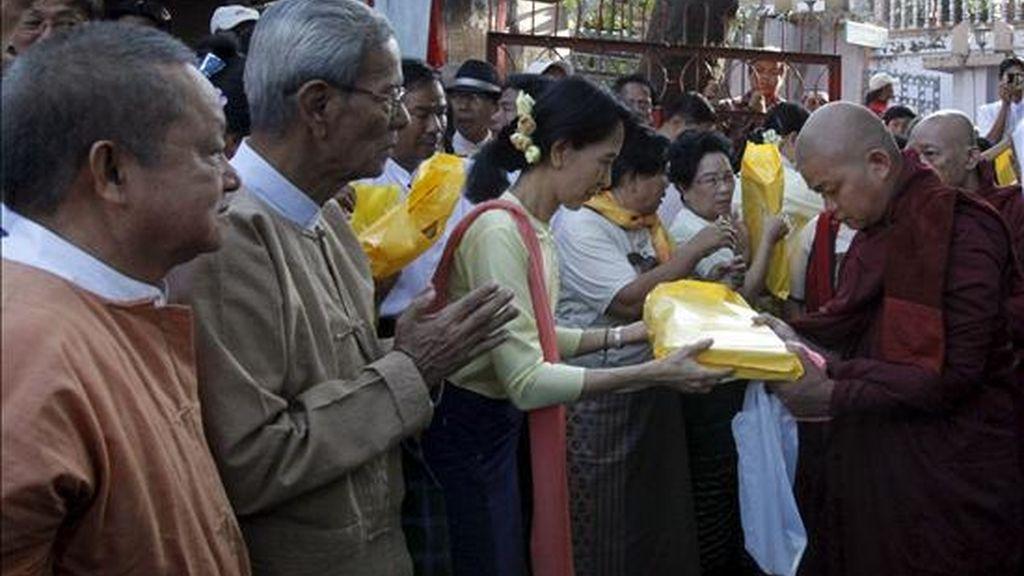 La líder opositora birmana y premio Nobel de la Paz , Aung San Suu Kyi (2-i), entrega hoy un presente a un monje Budista frente a su partido, la Liga Nacional por la Democracia (NLD), en Rangun, Birmania. EFE