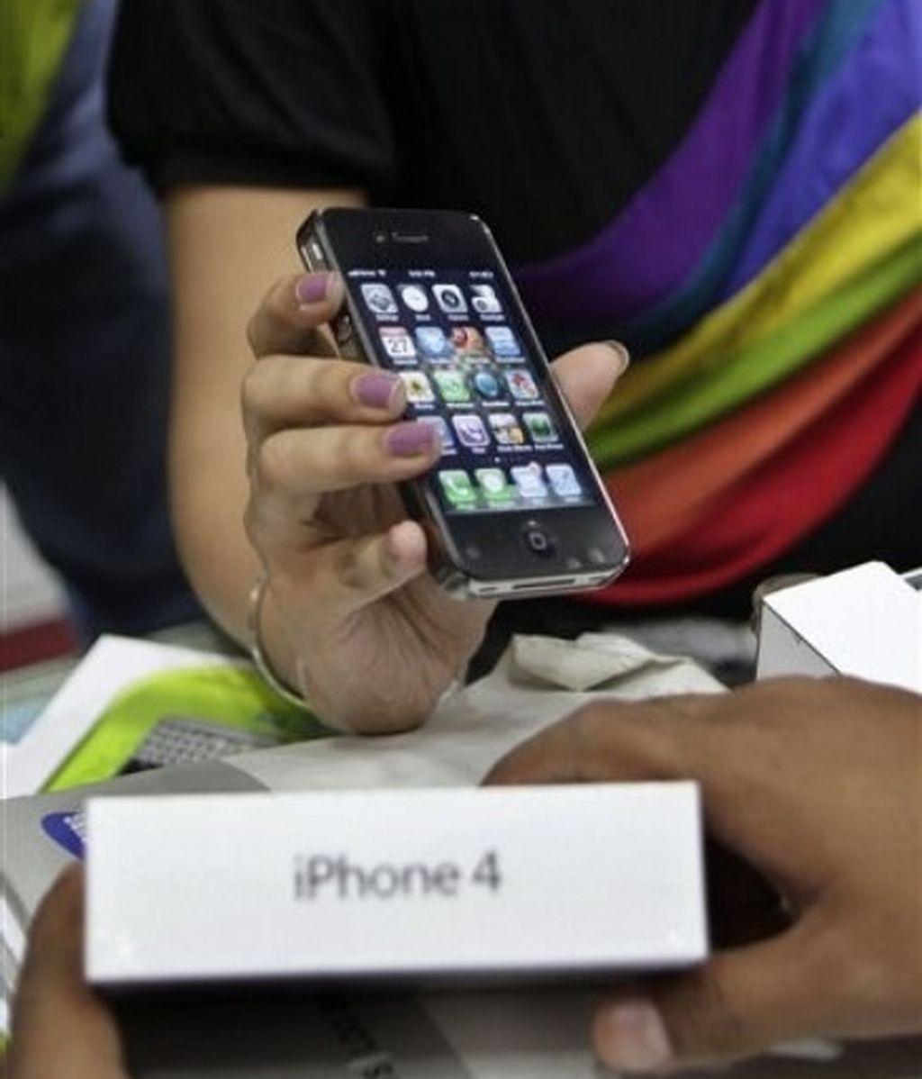 Una vendedora ofrece un iphone 4 en una tienda en Delhi. Foto: AP