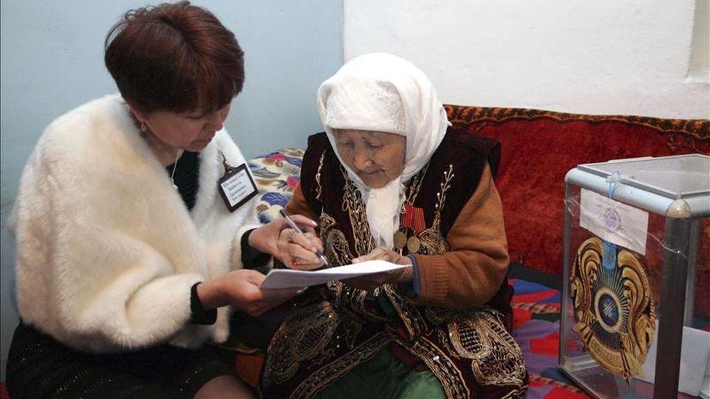 Una miembro de la mesa electoral ayuda a rellenar su papeleta a una anciana que votó en las elecciones presidenciales desde su propia casa, situada 80 km al sur de Almaty (Kazajistán), hoy, domingo 3 de abril de 2011. EFE