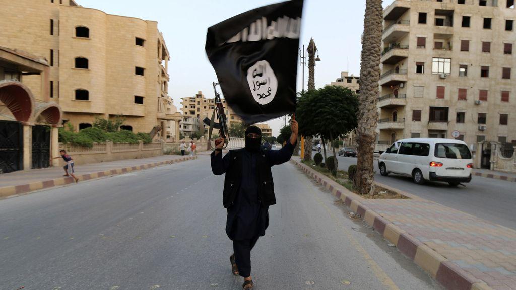 Un yihadista porta la bandera del Estado Islámico