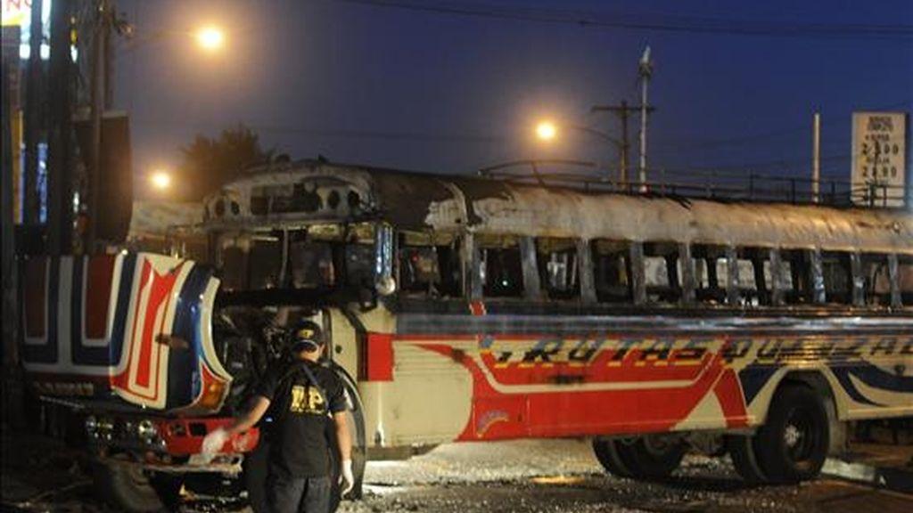 Un fiscal del Ministerio Público inspeccionan el autobús en el que impactó una bomba lanzada por desconocidos, en un sector del oeste de Ciudad de Guatemala. EFE
