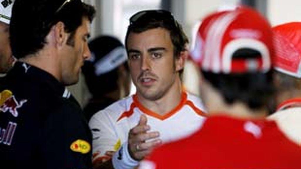 El piloto Fernando Alonso habla con el australiano Mark Webber. Foto: EFE