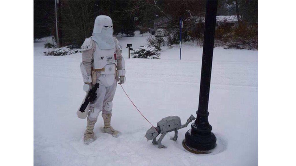 Un soldado sacando a pasear a su pequeño AT-AT