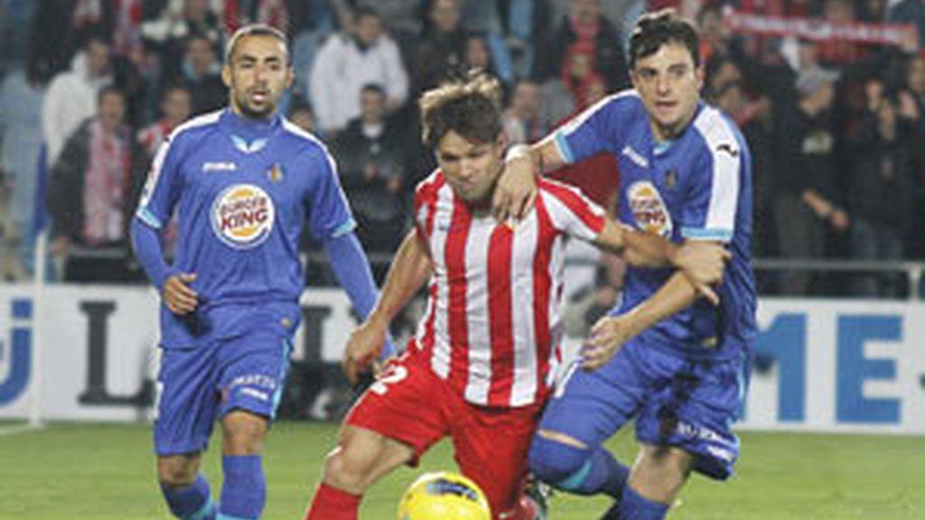 El Getafe pelea un balón con Diego Ribas FOTO: EFE