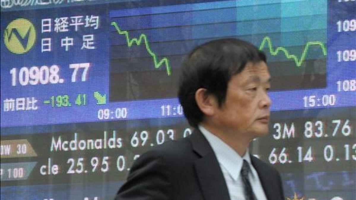 Un hombre de negocios japonés pasa junto a una pantalla que muestra la evolución del índice Nikkei de la Bolsa de Tokio. EFE/Archivo