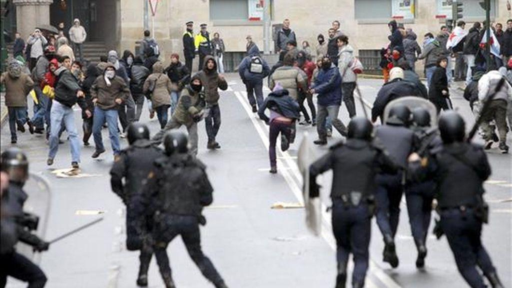 """La policía dispersa a un grupo de independentistas que arrojan botellas ante la manifestación convocada por el colectivo Galicia Bilingüe, y que ha concluido con la detención de ocho personas, en diferentes escaramuzas en las que dos policías resultaron heridos y se causaron destrozos al mobiliario urbano. La protesta había sido convocada para reclamar """"libertad de elegir"""" el gallego o el castellano en la escuela o en la administración, y que convocó una reacción de un grupo de independentistas, unos 250 según fuentes policiales. EFE"""