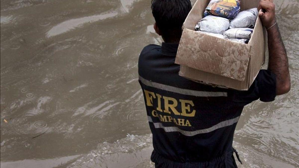 Un miembro del equipo de rescate carga una caja con provisiones para distribuirla entre la gente afectada por las inundaciones en Gampaha a 40 kilómetros de Colombo en Sri Lanka, resgistradas en mayo de 2010. EFE/Archivo